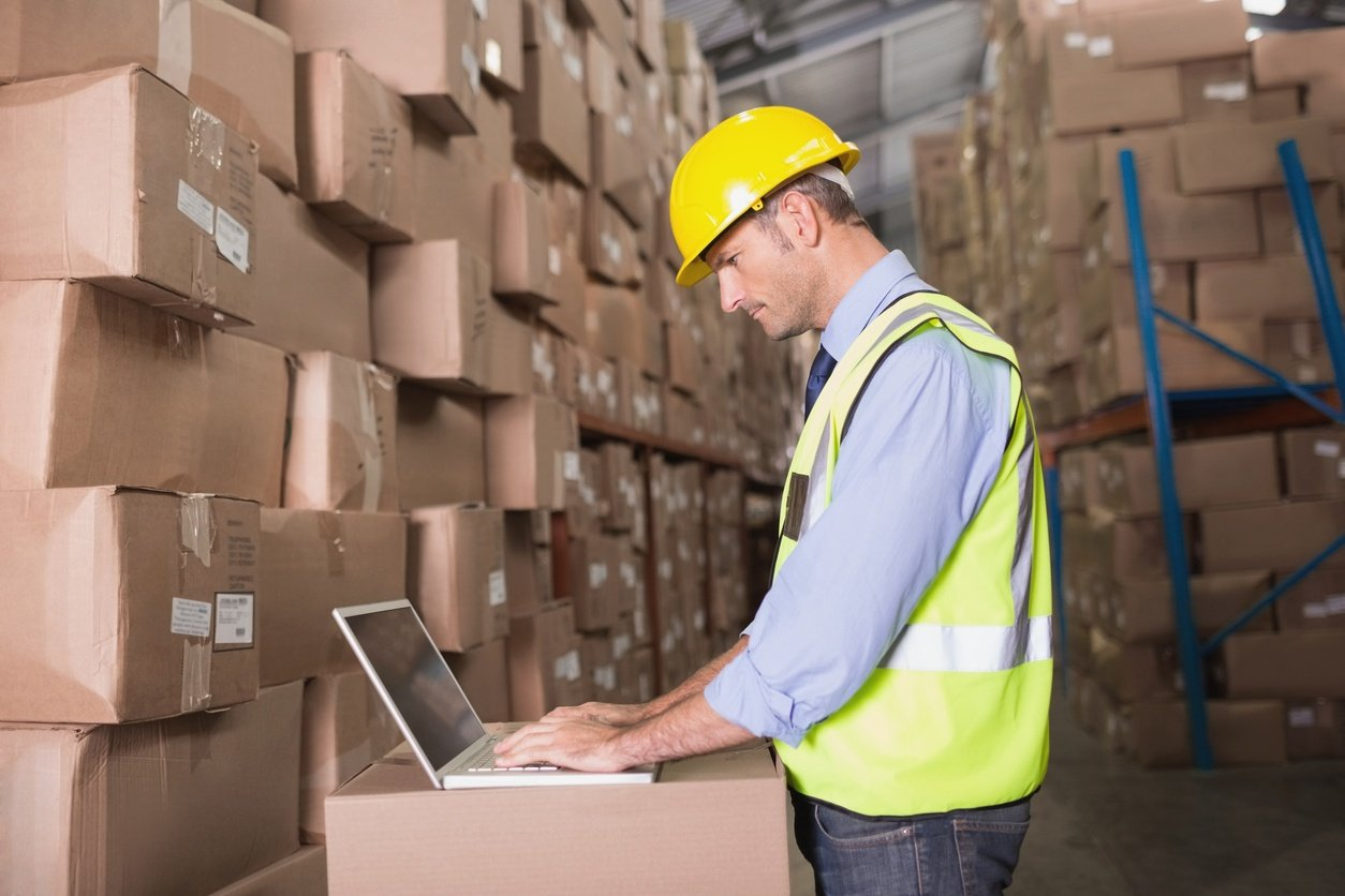 man on computer in warehouse